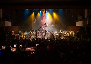 A long wide view of the orchestra on stage, yellow and blue lighting, audience members in the foreground