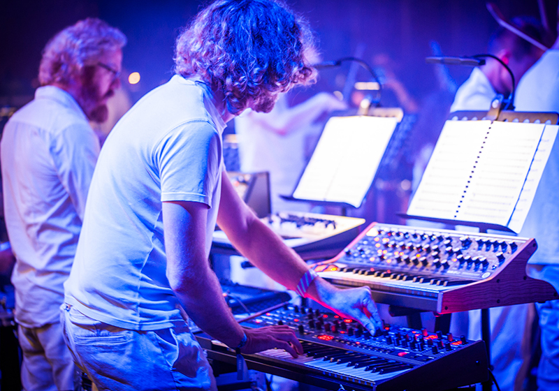 A rear shot of to people playing synthesisers on stage, hues of blue lighting
