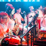 Side angle of musicians on stage, french horns, clarinet and bass clarinet, some musicians playing, lit in red and blue