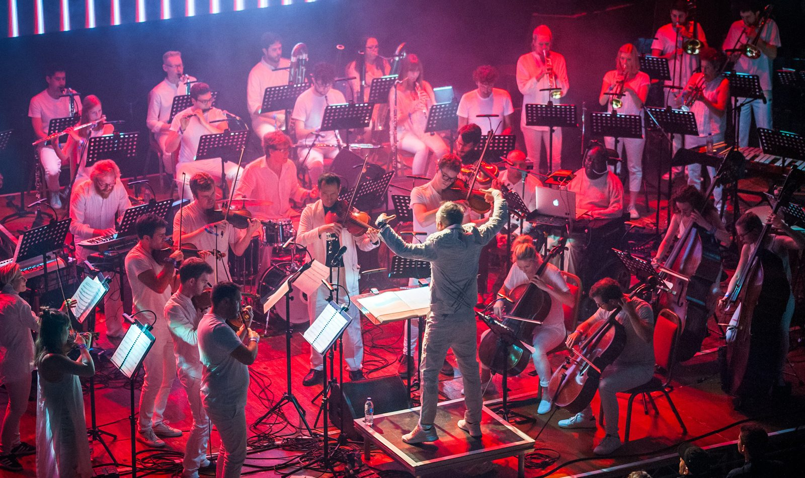 wide view of orchestra members playing on stage at Colston hall, dramatic red lights, Charles Hazlewood conducts with his back to the camera