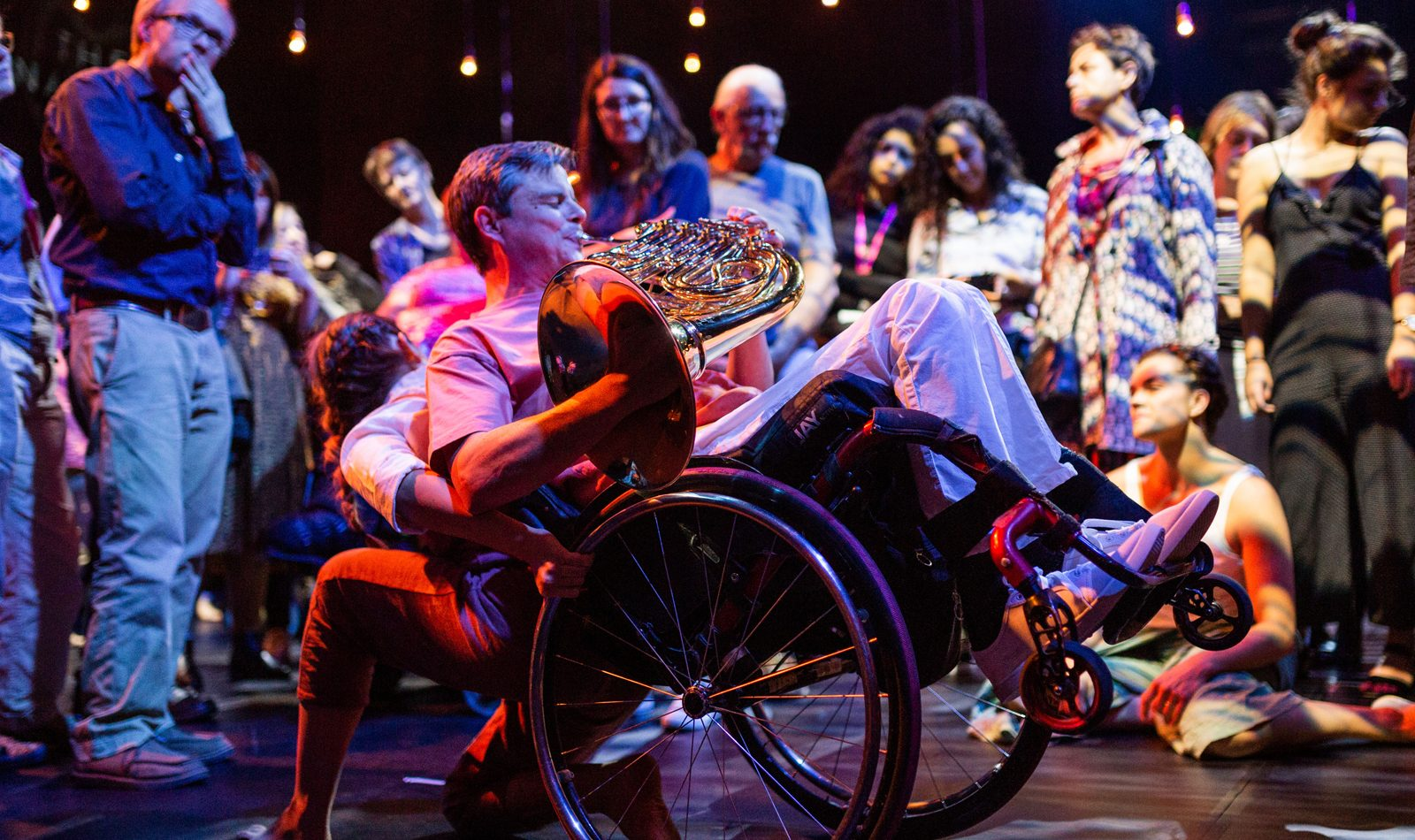 A male french horn player plays amongst an audience on stage. A partially obscured femal dancer takes the weight of his wheelchair, tipping him back so that he is on two wheels.