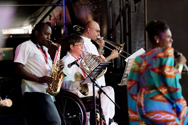 A saxophonist, french horn player, (Guy LLewelyn) and a trombonist on stage playing