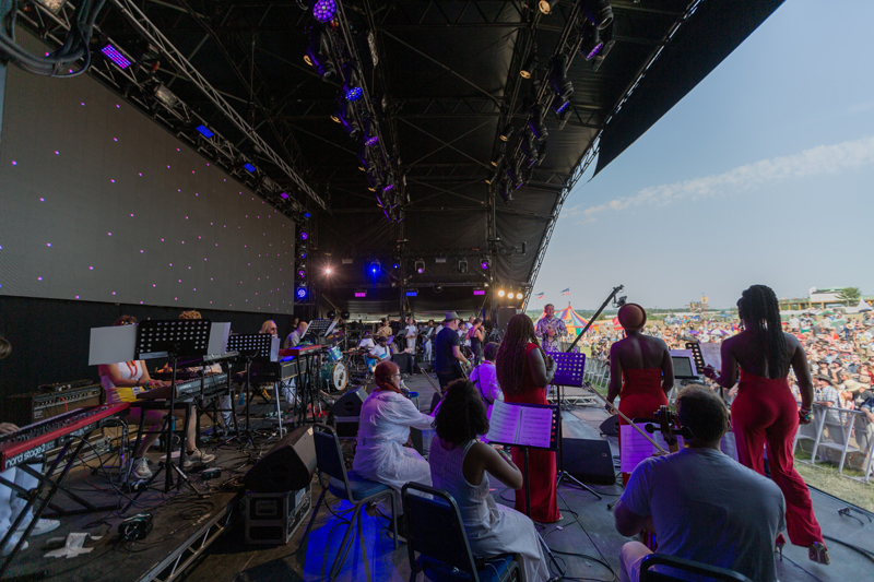 wide, side angle of The Love Unlimited Synth Orchestra on stage, crowd in the background