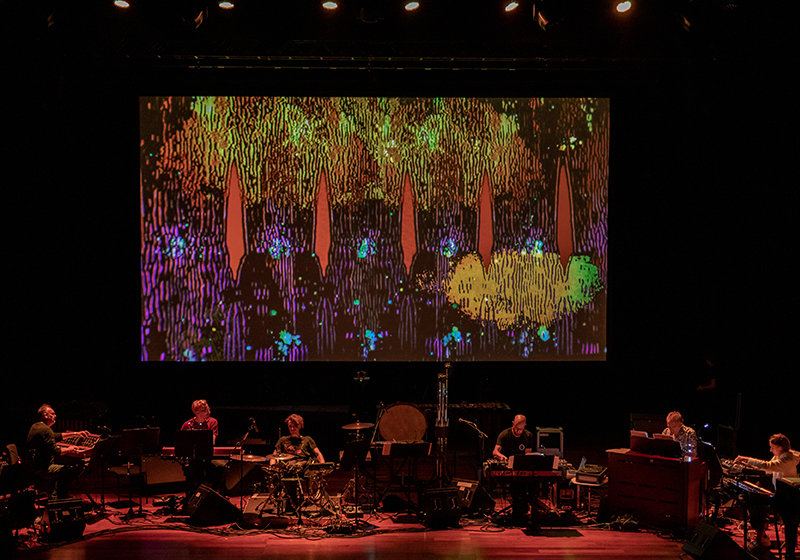 8 musicians on stage playing, warm but dark lighting, a large screen behind displays psychedelic imagery