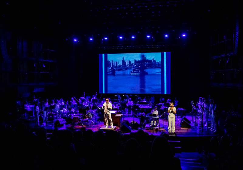 Large Orchestra play on a dimly lit stage, purple lighting, conductor leads from the front, a large screen behind displays a river and buildings
