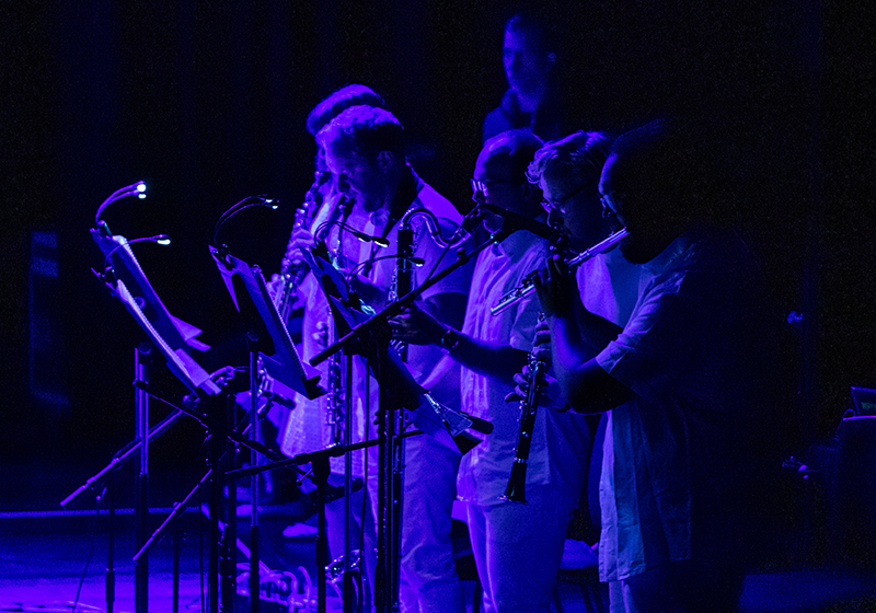 musicians in white play a flute, clarinet and bass clarinet, purple lighting