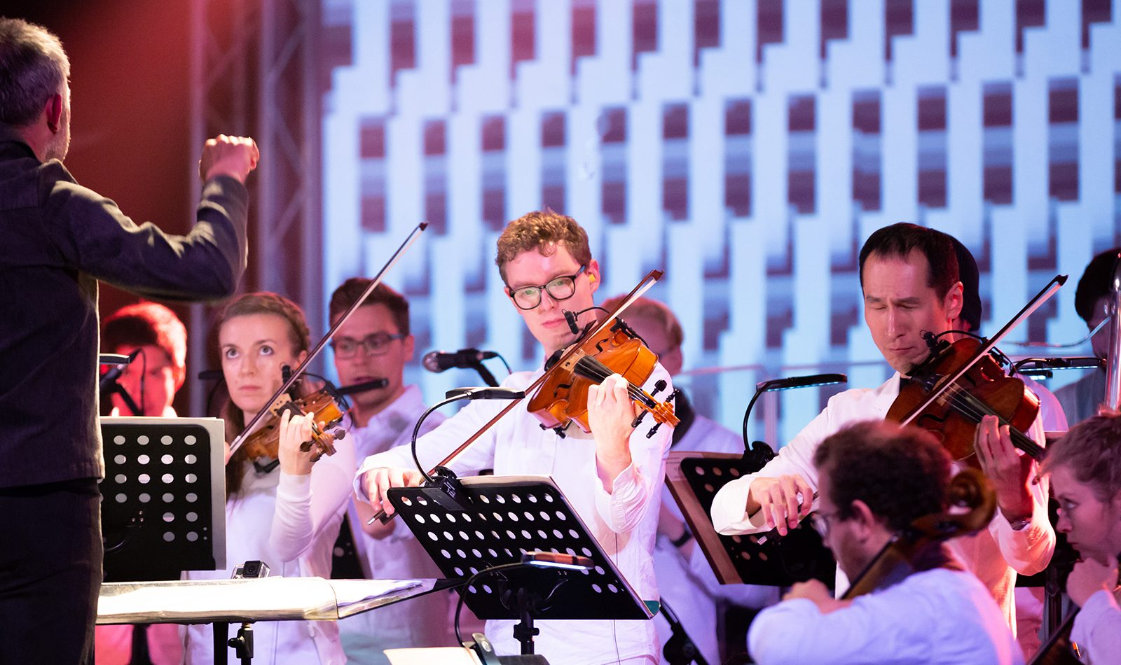8 string players in an orchestra, dressed in white, bright lights on screen behind