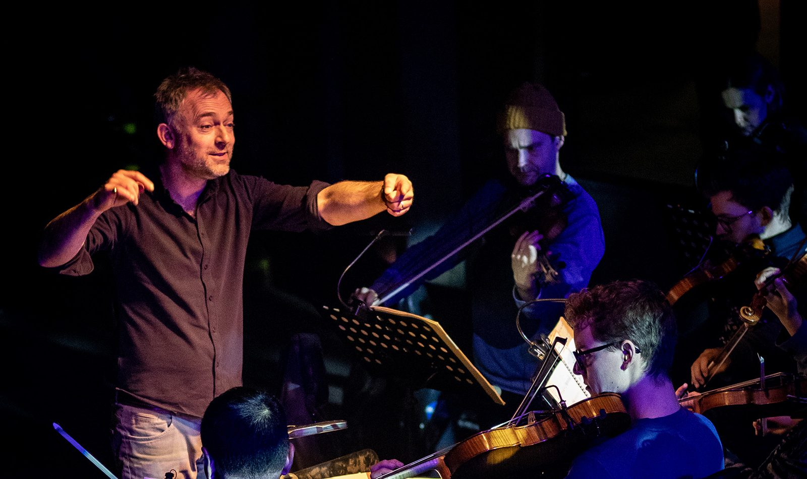 A man in a casual shirt conducts, smiling. String players in the foreground.