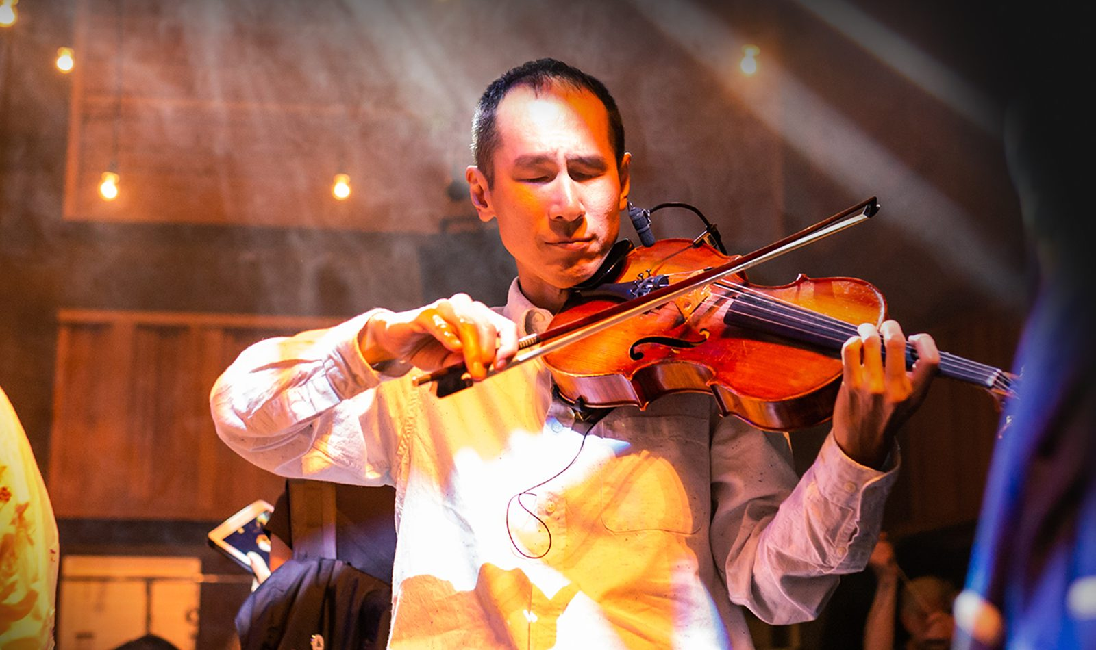 A man plays violin, warm atmospheric lighting