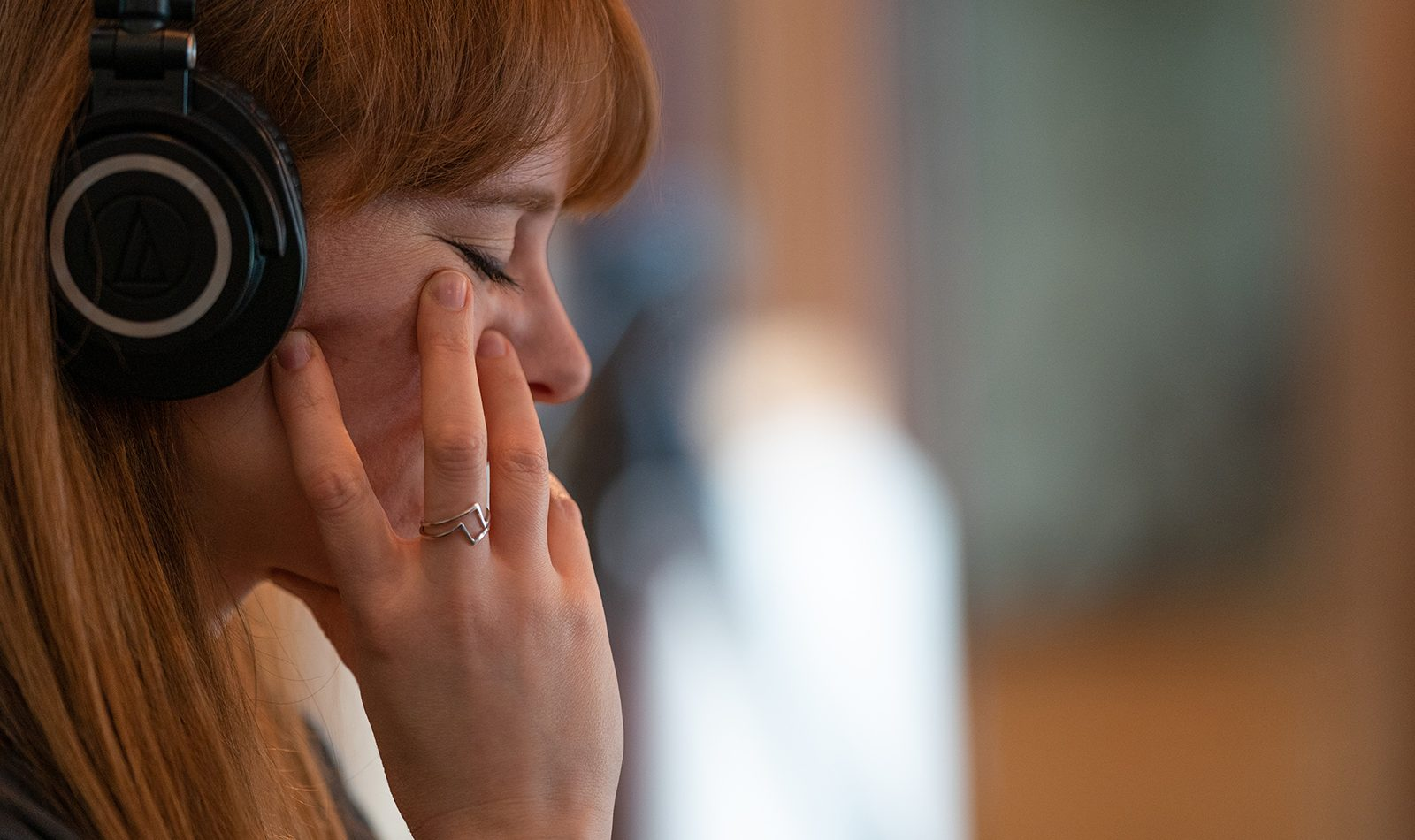 Side profile of a caucasian woman with red hair, she wears headphones and has her eyse closed looking pensive