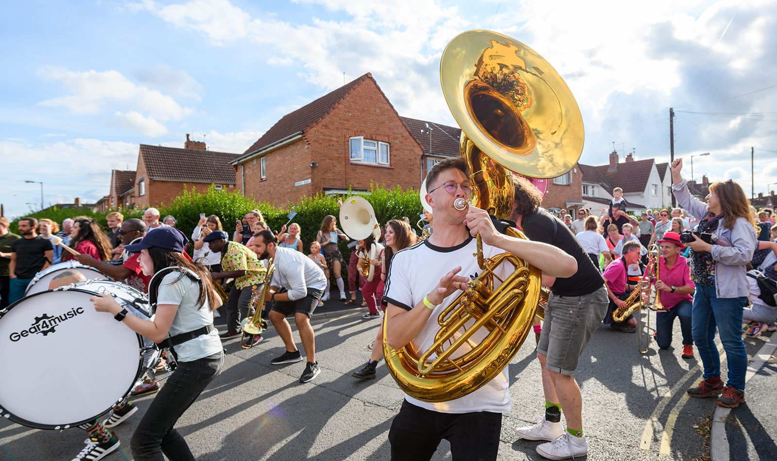 A crowd of people, musicians, a white male plays sousaphone